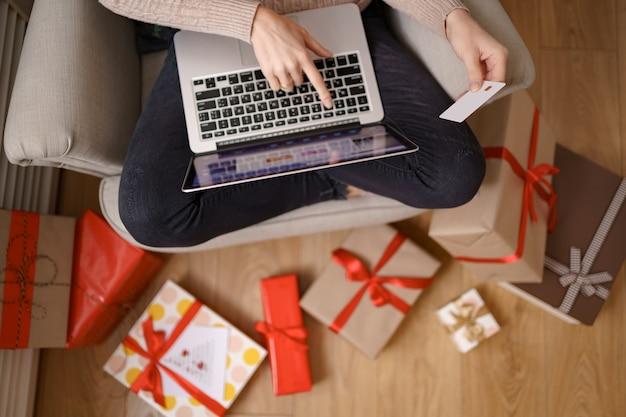 Imagem de mulher simpática e satisfeita segurando um cartão de crédito com espaço de cópia usando um laptop