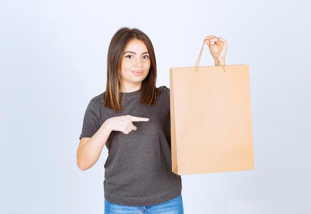 Imagem de mulher sorridente, apontando para um saco de papel e posando.
