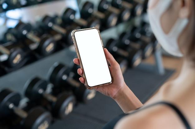 Imagem de mulher usando máscara facial e a mão segurando um telefone celular com tela branca no ginásio.