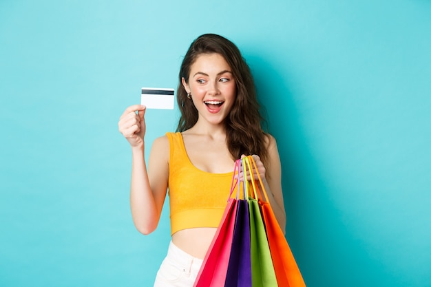 Imagem de mulher viciada em compras, mostrando seu cartão de crédito de plástico, segurando sacolas de compras, vestindo roupas de verão, em pé contra um fundo azul.
