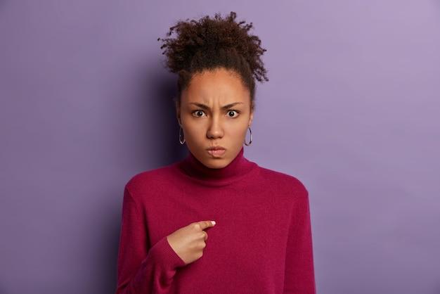 Imagem de mulher zangada decepcionada indica consigo mesma, irritada por ser selecionada, sorri maliciosamente, tem cabelo cacheado penteado, usa gola olímpica, isolada em parede roxa, parece irritada por ser acusada