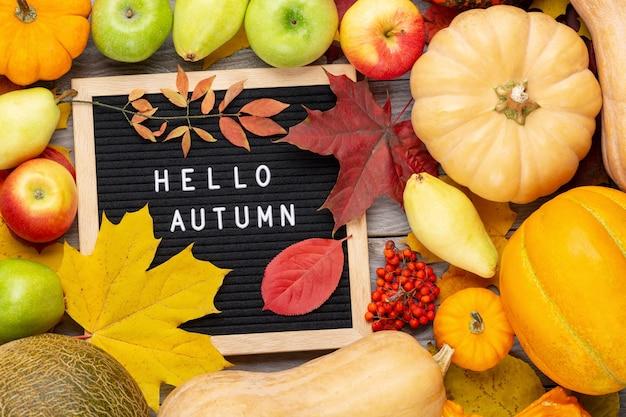 Imagem de natureza morta de outono com abóboras, ashberry, peras, maçãs, folhagem colorida e quadro de correio com palavras olá outono.