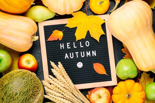 Imagem de natureza morta de outono com melão, maçãs, peras, centeio, abóboras, folhagem colorida e cartolina com palavras olá outono