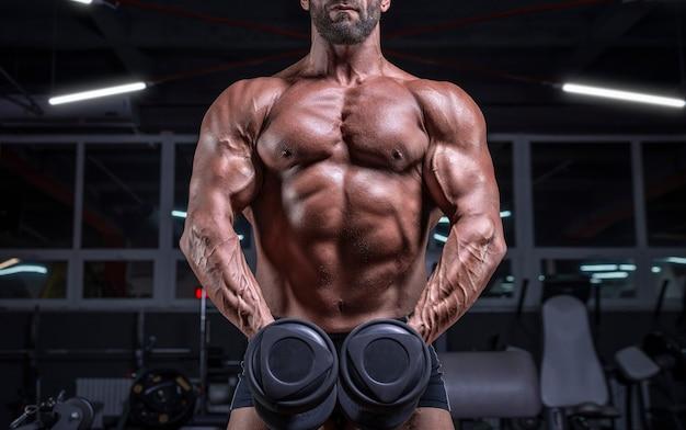 Imagem de noname de um atleta poderoso bombeando bíceps com halteres no ginásio. conceito de fitness e musculação. mídia mista