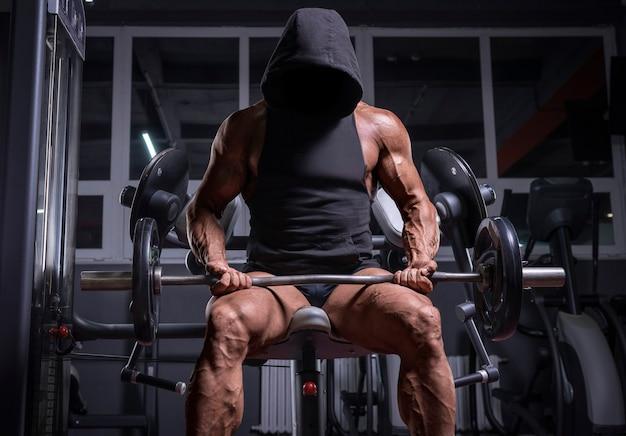 Imagem de noname de um atleta poderoso em um moletom, sentado em um banco em uma academia. conceito de fitness e musculação. mídia mista