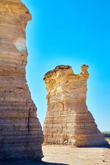 Imagem de obeliscos de rocha branca saindo de um deserto plano