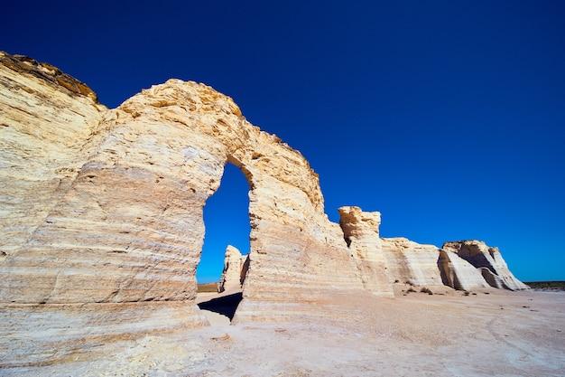 Imagem de olhando para cima para pilares de rocha brancos com arco e céu azul brilhante