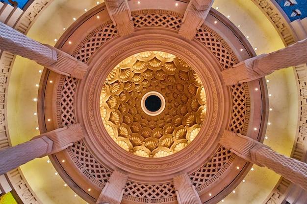 Imagem de olhando para o teto com conchas douradas e cercado por grandes pilares