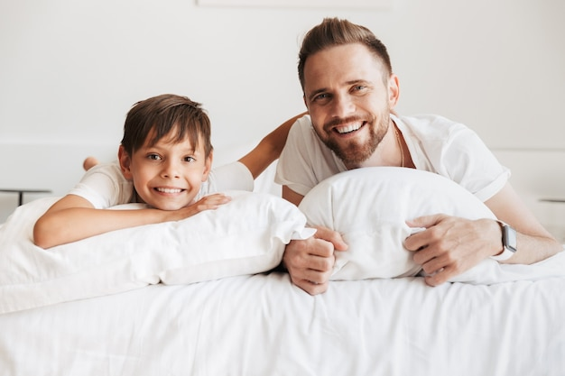 Imagem de pai alegre e filho rindo, enquanto deitado na cama com linho branco em casa e olhando para você