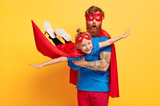 Imagem de pai e filha ruivos vestidos de super-heróis