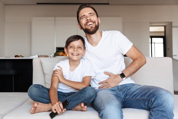 Imagem de pai e filho europeus rindo, sentados no sofá interno com controle remoto