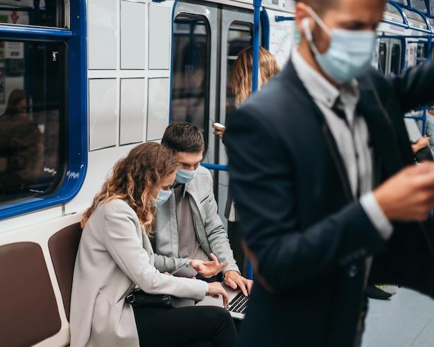 Imagem de passageiros com máscaras protetoras em um vagão do metrô
