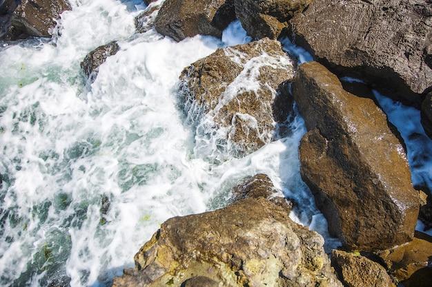 Imagem de pedras no mar com ondas, vista aérea