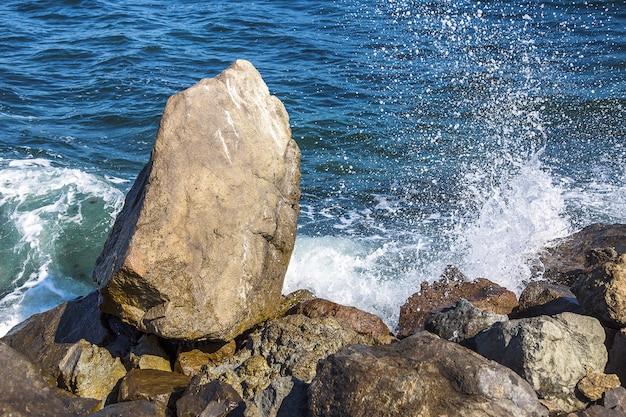 Imagem de pedras no mar com ondas, vista da costa
