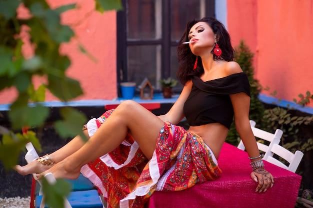 Imagem de perfil de uma jovem morena sexy em vermelho como uma cigana deitada à mesa de madeira, fumando.