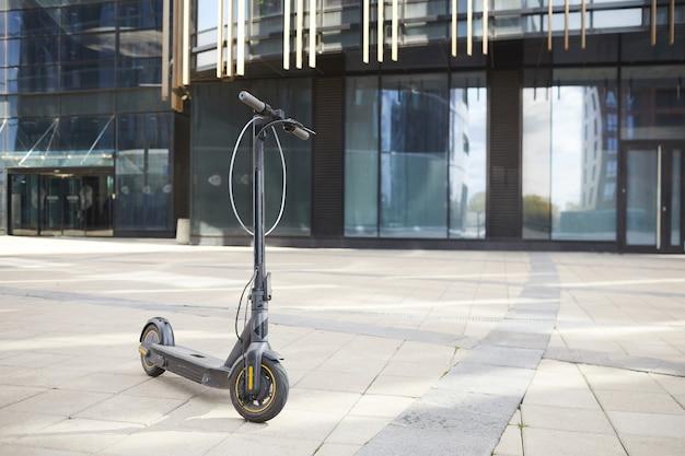 Imagem de plano de fundo de grande angular de uma scooter elétrica preta em um piso de cerâmica contra um prédio de vidro em um ambiente urbano.