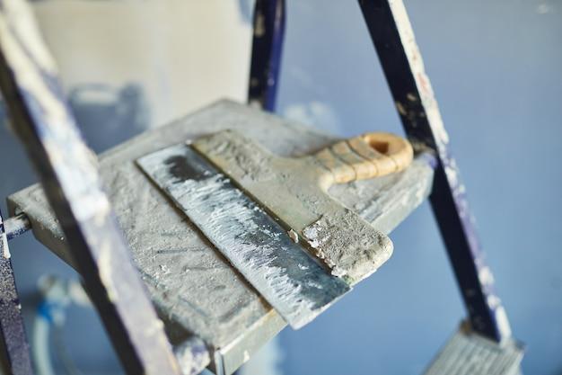 Imagem de plano de fundo próxima de uma espátula usada deitada no topo da escada no canteiro de obras ou na construção de uma casa, copie o espaço