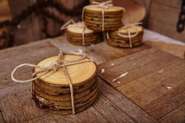 Imagem de quatro pacotes de bases para copos de madeira rústicas em um produto de exibição de superfície de madeira