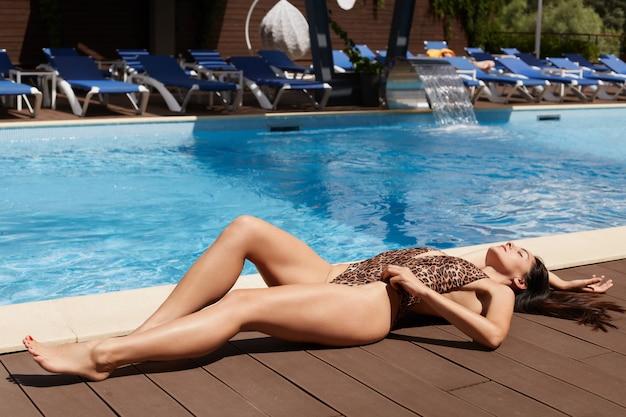Imagem de relaxado magro sexy morena tomando banho de sol, deitado perto da piscina, vestindo roupas de banho estampadas de leopardo, fechando os olhos, passando o tempo livre sozinho, estar no spa resort. relaxe o conceito