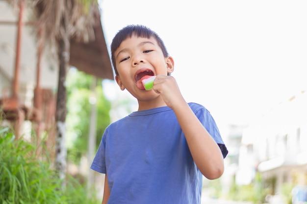 Imagem de retrato de criança de 6 a 7 anos. menino feliz criança asiática comendo e mordendo um sorvete vermelho. temporada de verão, sentimento delicioso, rosto desleixado de infância.