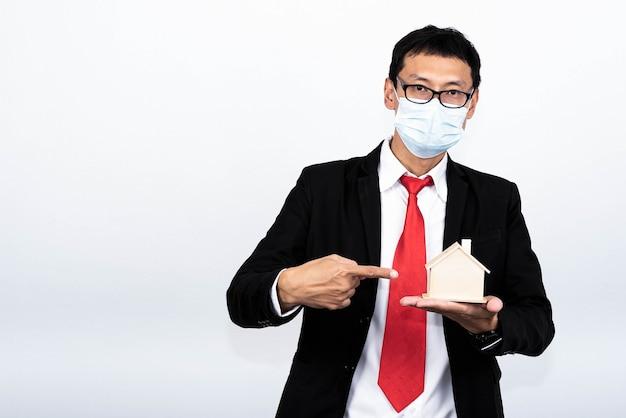 Imagem de retrato de homem de negócios asiático segurando e mostrar modelo caseiro em fundo branco