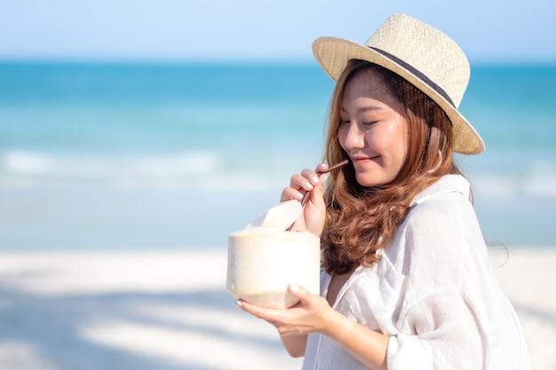 Imagem de retrato de uma linda mulher asiática segurando e bebendo suco de coco na praia