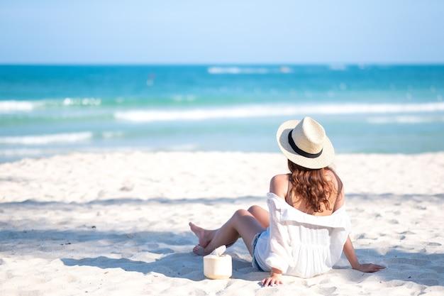 Imagem de retrato de uma linda mulher asiática, sentando-se e bebendo suco de coco na praia