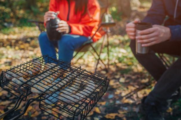 Imagem de salsichas cozidas na fumaça. eles estão na grelha. há duas pessoas sentadas em cadeiras dobráveis e segurando garrafas térmicas.
