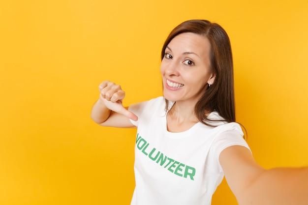 Imagem de selfie de mulher satisfeita sorridente feliz em t-shirt branca com voluntário de título verde de inscrição escrita isolado em fundo amarelo. ajuda de assistência gratuita voluntária, conceito de trabalho de graça de caridade.