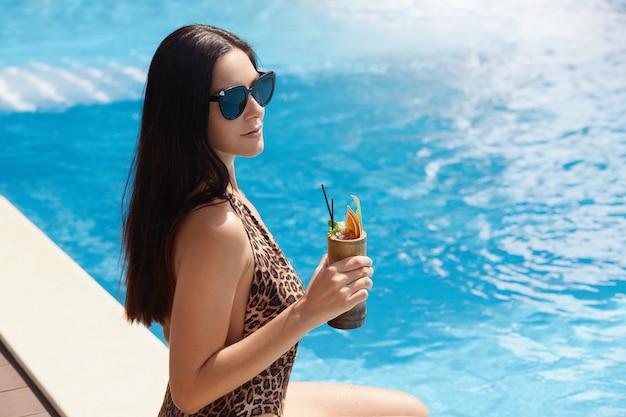 Imagem de slim desportiva morena sexy com cabelos longos, usando óculos escuros e leopardo impresso maiô, segurando o cocktail em uma mão, sentado perto da piscina, relaxante. conceito de tempo de férias.