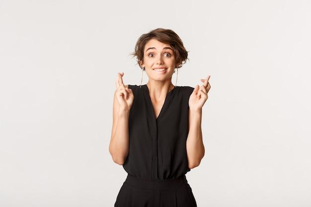 Imagem de sortuda linda garota mordendo o lábio e dedos cruzados esperançoso, fazendo desejo sobre o branco.