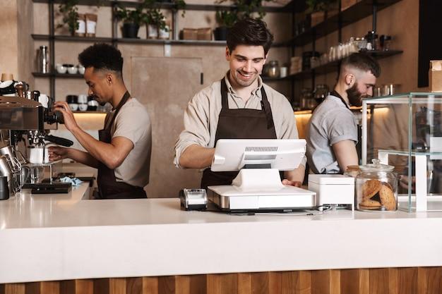 Imagem de três colegas de homens de café felizes no café bar trabalhando dentro de casa.