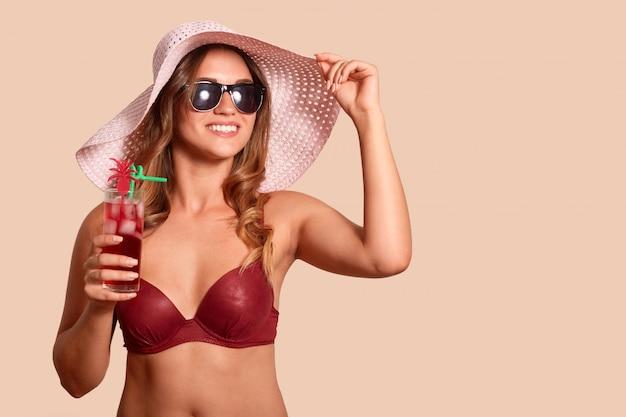 Imagem de turista bonito alegre usando chapéu de palha, maiô vermelho e óculos de sol, olhando de lado, aproveitando as férias de verão, segurando um copo de coquetel frio. copie o espaço para propaganda.