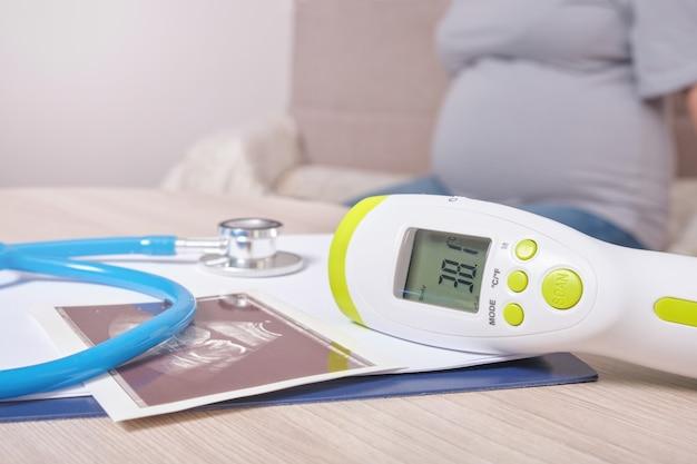 Imagem de ultrassom, estetoscópio e termômetro na mesa, doença grávida
