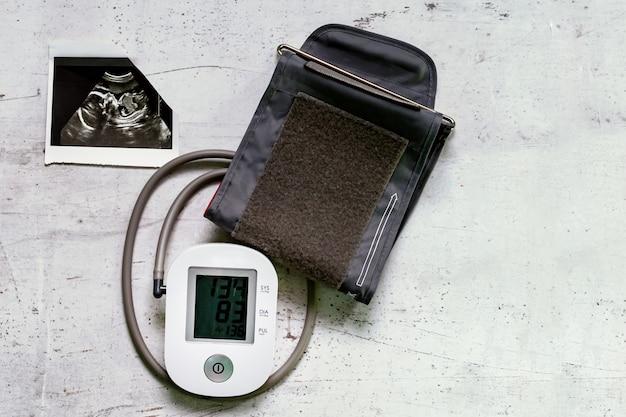 Imagem de ultrassonografia da 20ª semana de gestação e de um monitor de pressão arterial