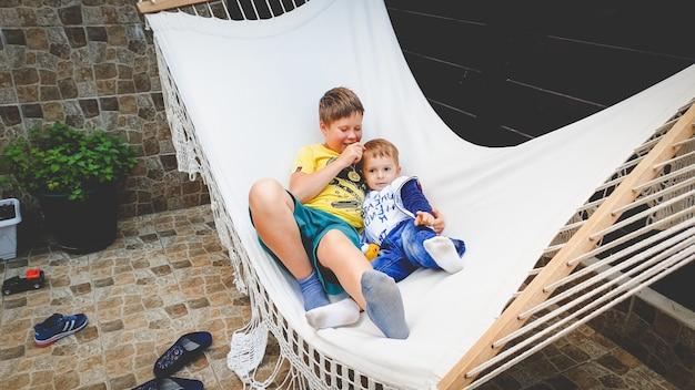 Imagem de um adolescente sentado e balançando em uma rede com seu irmão mais novo no quintal de uma casa