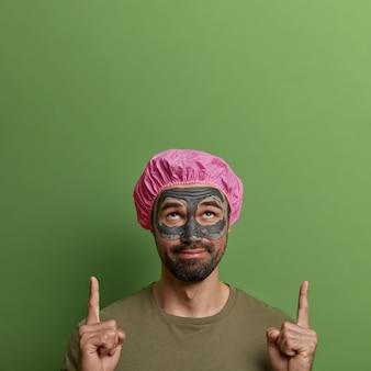 Imagem de um adulto curioso barbudo com máscara de lama de beleza no rosto, indica para cima com os dois dedos indicadores, anuncia produto cosmético, usa touca de banho, olha para cima, isolado na parede verde