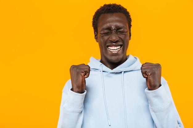 Imagem de um afro-americano feliz com um moletom streetwear sorrindo e gesticulando como vencedor
