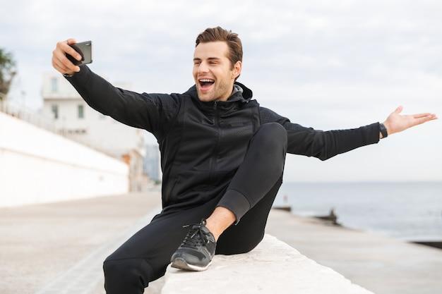 Imagem de um alegre esportista dos anos 30 em uma roupa esportiva preta, tirando uma foto de selfie no celular enquanto está sentado no calçadão à beira-mar