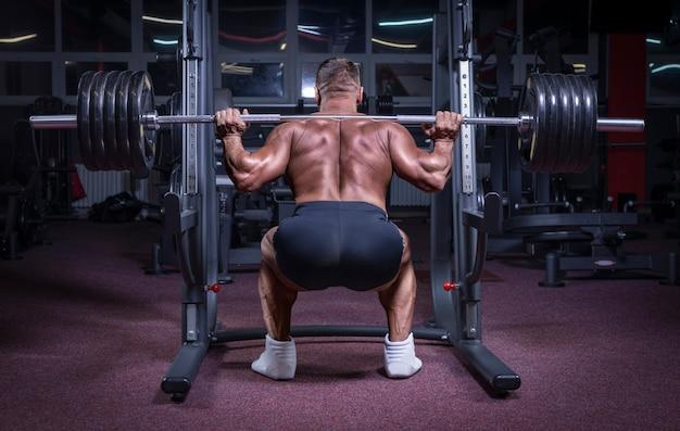Imagem de um atleta poderoso agachado com uma barra em uma academia. conceito de fitness e musculação. mídia mista