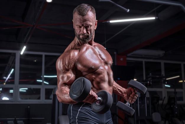 Imagem de um atleta poderoso bombeando bíceps com halteres no ginásio. conceito de fitness e musculação. mídia mista