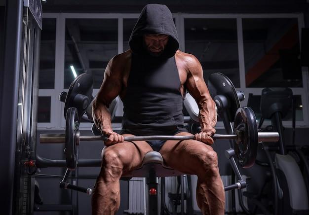 Imagem de um atleta poderoso em um moletom, sentado em um banco em uma academia. conceito de fitness e musculação. mídia mista