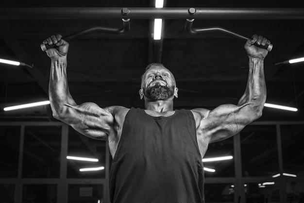 Imagem de um atleta poderoso fazendo flexões na academia. bombeamento de volta. conceito de fitness e musculação. mídia mista