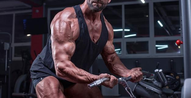 Imagem de um atleta poderoso se exercitando em um crossover na academia. bombeamento de bíceps. conceito de fitness e musculação. mídia mista