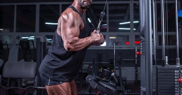 Imagem de um atleta poderoso se exercitando em um crossover na academia. bombeamento de tríceps. conceito de fitness e musculação. mídia mista