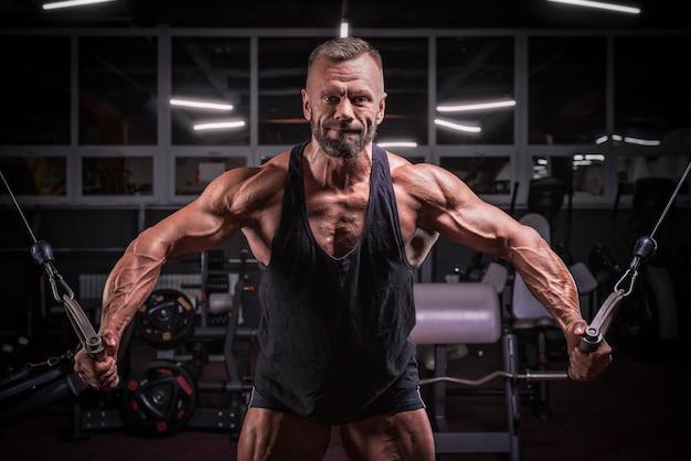 Imagem de um atleta poderoso se exercitando em um crossover na academia. conceito de fitness e musculação. mídia mista