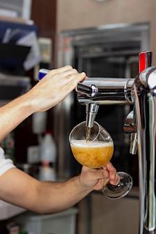 Imagem de um barman servindo chope em um copo em um bar ou restaurante