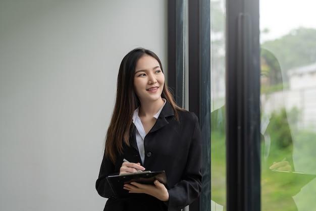 Imagem de um belo empresário asiático em pé no escritório segurando o documento.