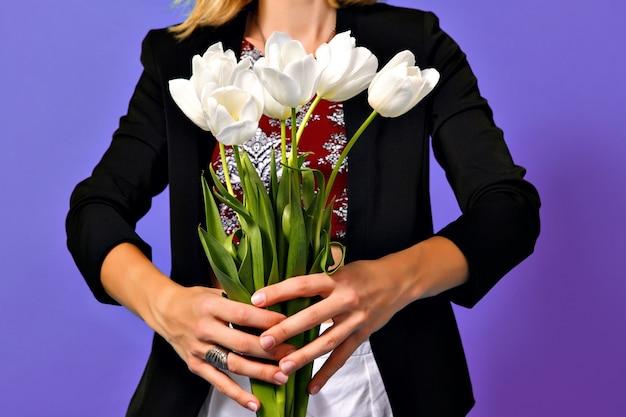 Imagem de um buquê de tulipas brancas nas mãos de uma jovem elegante numa jaqueta preta, isolada no fundo roxo.