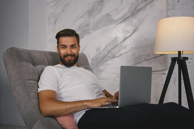 Imagem de um cara atraente com barba espessa desfrutando de comunicação online via redes sociais, usando conexão de alta velocidade à internet em laptop pc, olhando para câmera com sorriso confiante e satisfeito
